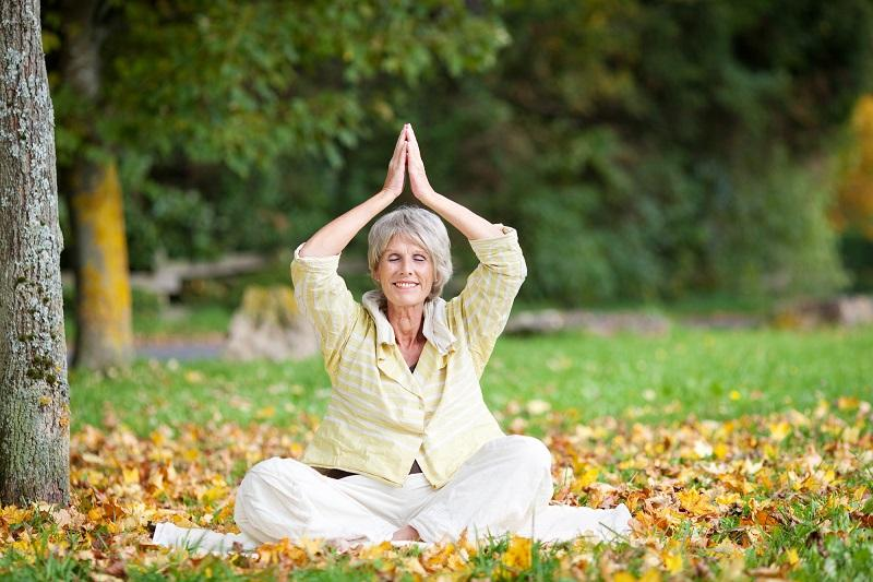 smiling-senior-woman-with-hands-clasped-meditating