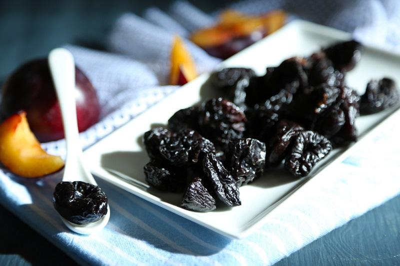 fresh-and-dried-plums-on-napkin-on-wooden-background-2