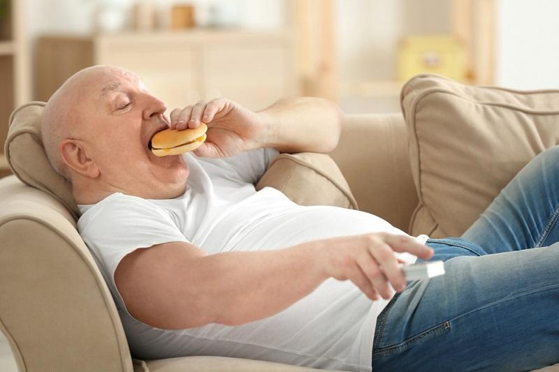fat-senior-man-watching-tv-and-eating-hamburger-while-lying-on-sofa-at-home-sedentary-lifestyle-concept