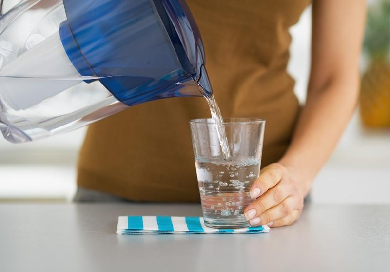 closeup-on-housewife-pouring-water-into-glass-from-water-filter-pitcher