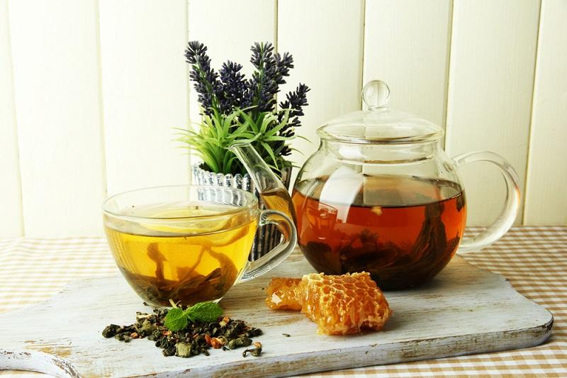 cup-and-teapot-of-green-tea-with-honey-on-table-on-wooden-background