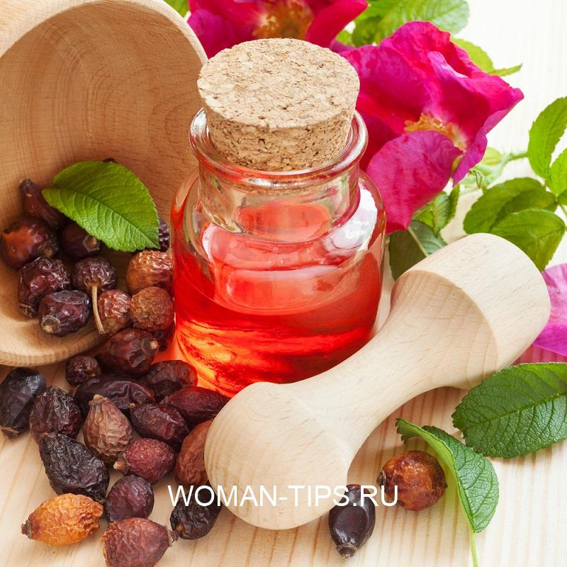 essential-oil-in-glass-bottle-dried-rose-hip-berries-in-wooden