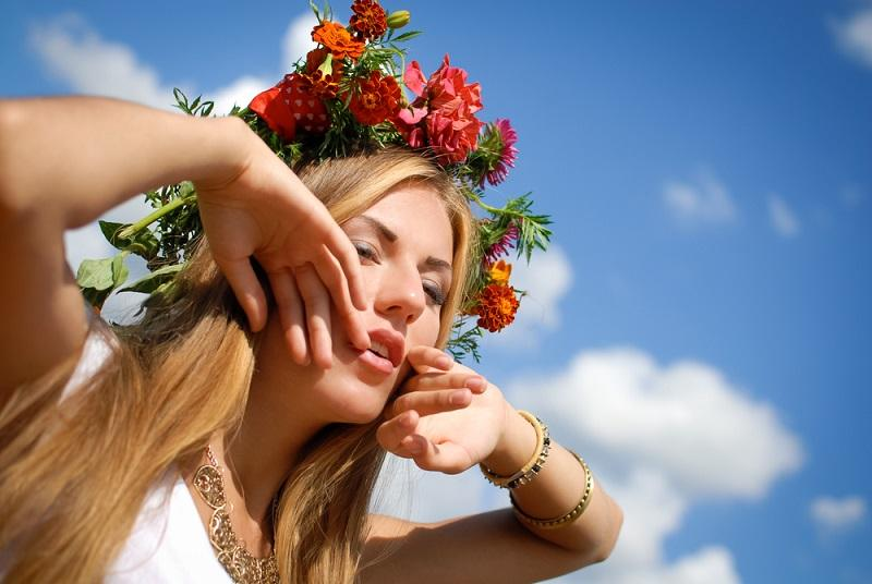 sexy-beautiful-girl-in-marigold-wreath-with-raised-hands-on-sky-background
