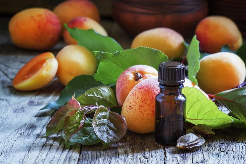 essential-oil-of-apricot-pits-and-fresh-apricots-with-leaves-v